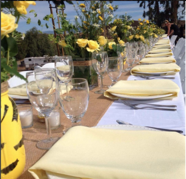 Set up of a rustic, banquet, long style seating with a pop of yellow buttercup linen napkins and burlap runners dressed with the guest place settings.  All ready to go; awaiting the bridal party festivities to begin.